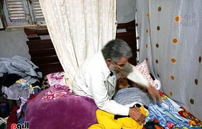 """الأب الفدائى.. """"الهادى"""" 60 عاما يحمل ابنه المريض على صدره كل يوم بحثا عن علاجه.. 17 سنة يحمل الهم ولا يجد من يساعده.. ويؤكد: زوجتى مصابة بشلل وابنى الحسن يعانى من تيبس فى العضلات وبعت كلما أملك.. صور"""